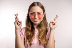 La jeune femme impressionnante a habillé croiser en passant ses doigts photos stock