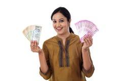 La jeune femme indienne tenant la devise note l'agianst blanc Photographie stock