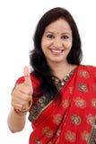 La jeune femme indienne traditionnelle gaie montrant des pouces lèvent le gestur photos stock