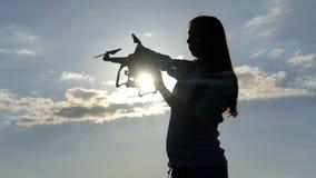 La jeune femme insère une batterie dans un quadracopter au coucher du soleil dans le ralenti clips vidéos