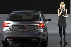 La jeune femme introduit la Chrysler neuve 300S Photographie stock