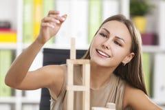La jeune femme joue avec les briques en bois Photos stock