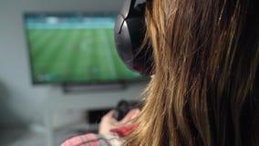 La jeune femme joue le jeu vidéo utilisant un gamepad closeup banque de vidéos