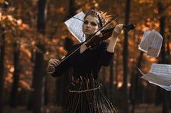 La jeune femme joue le violon au-dessus des notes de vol de musique Images libres de droits
