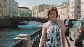 La jeune femme joyeuse dans la robe repérée chante au remblai au vieux centre de la ville banque de vidéos