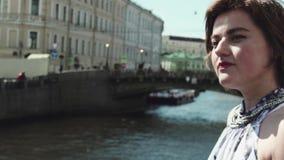 La jeune femme joyeuse dans la robe repérée se penche sur la barrière à la rive dans la vieille ville clips vidéos
