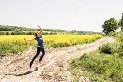 La jeune femme joyeuse saute dans le domaine de graine de colza Photographie stock