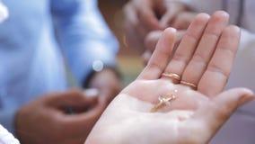 La jeune femme juge la croix d'or disponible avant cérémonie de baptême dans l'église banque de vidéos