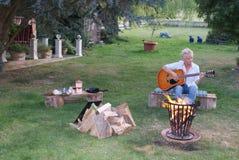 La jeune femme laisse toutes les inquiétudes derrière et fait la musique sur la guitare image libre de droits