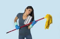 La jeune femme latine heureuse attirante dans les gants de lavage tenant le balai ayant l'amusement chantant et jouant Air guitar Photographie stock