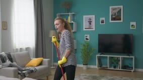 La jeune femme lave le plancher en appartement et chante une chanson dans le balai comme un microphone banque de vidéos