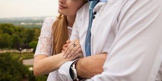 La jeune femme lie des bras avec son homme Photo stock