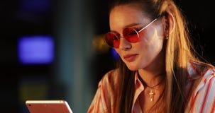 La jeune femme lit quelque chose dans ses tables se reposant à la table en café dehors banque de vidéos