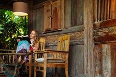 La jeune femme a lu le livre de papier sur la véranda extérieure Image stock