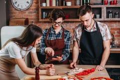 La jeune femme lui enseignent des amis cuisson Les gens ayant l'amusement tandis que p Photos libres de droits