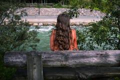 La jeune femme méconnaissable s'assied sur un banc près d'une rivière de montagne images libres de droits