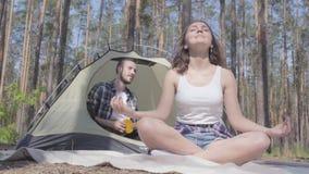 La jeune femme méditant dans le premier plan tandis que l'homme jouant l'ukulélé sur le fond se reposant dans la tente aimer banque de vidéos