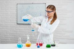 La jeune femme mélange les liquides chimiques colorés photographie stock libre de droits