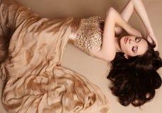 La jeune femme magnifique avec le maquillage de cheveux foncés et de soirée, porte la robe luxueuse photo stock