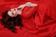La jeune femme magnifique avec le maquillage de cheveux foncés et de soirée, porte la robe luxueuse photo libre de droits