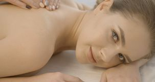 La jeune femme magnifique avec la peau fraîche et le maquillage naturel regarde in camera avec le sourire tout en recevant le mas clips vidéos