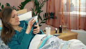 La jeune femme malade mesurent sa température et font l'appel téléphonique à son docteur de patron banque de vidéos
