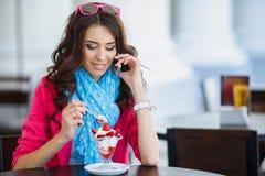 La jeune femme mange le dessert et parler au téléphone Images libres de droits