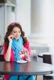 La jeune femme mange le dessert et parler au téléphone Photographie stock
