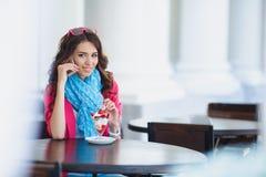 La jeune femme mange le dessert et parler au téléphone Images stock