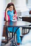 La jeune femme mange le dessert et parler au téléphone Image libre de droits
