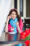 La jeune femme mange le dessert et parler au téléphone Photos stock