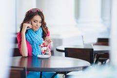 La jeune femme mange le dessert et parler au téléphone Photographie stock libre de droits