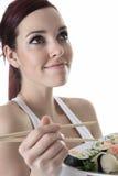 La jeune femme mangeant un sushi rapiècent contre un blanc photographie stock libre de droits