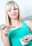 La jeune femme mangent du yaourt dans une cuisine Photographie stock