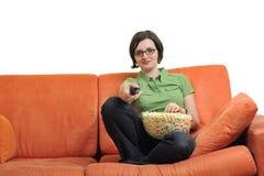 La jeune femme mangent le maïs éclaté et la TV de observation Photographie stock libre de droits