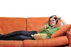 La jeune femme mangent le maïs éclaté et la TV de observation Photo stock