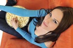 La jeune femme mangent le maïs éclaté et la TV de observation Photo libre de droits