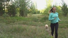 La jeune femme marche avec le chien dans la forêt banque de vidéos