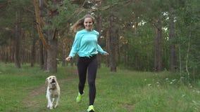 La jeune femme marche avec le chien dans la forêt clips vidéos