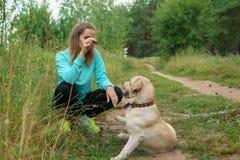 La jeune femme marche avec le chien dans la forêt Image libre de droits