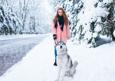 La jeune femme marche en parc avec le chien de traîneau sibérien Image libre de droits