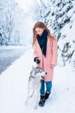 La jeune femme marche en parc avec le chien de traîneau sibérien Photographie stock