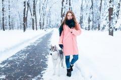 La jeune femme marche en parc avec le chien de traîneau sibérien Photographie stock libre de droits