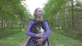 La jeune femme marche en parc avec un chat dans un sac à dos banque de vidéos