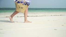 La jeune femme marche nu-pieds sur la plage le long de l'océan banque de vidéos