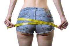 La jeune femme mesure les fesses avec une bande de mesure, isolat Image libre de droits