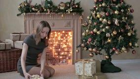 La jeune femme met des cadeaux sous l'arbre de Noël banque de vidéos