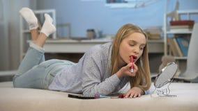 La jeune femme mettant sur le rouge à lèvres rouge, désir adulte de regard, améliorent l'aspect banque de vidéos