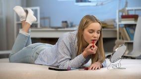 La jeune femme mettant sur le rouge à lèvres rouge, désir adulte de regard, améliorent l'aspect images stock