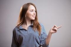 La jeune femme mignonne dirige un doigt loin sur un fond gris-clair avec l'espace de copie ou le texte, la publicité, image Roux  photo stock